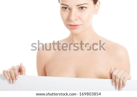 Topless woman holding copy space. Isolated on white.