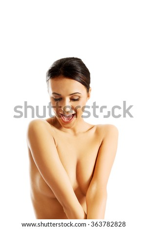 Topless woman sitting on desk, touching her neck