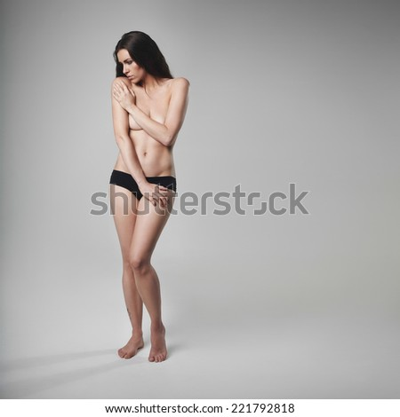 Topless young woman looking down while covering her breasts. Young beautiful naked woman covering her breast over grey background with lots of copy space. - stock photo
