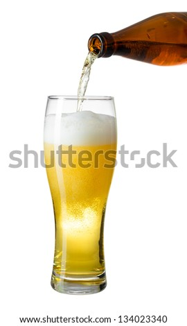 Topping up light beer from bottle to glass isolated on white