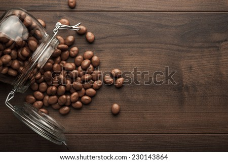 topple over glass jar full of chocolate sweets background