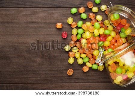 toppled over glass jar full of colorful sweets on the wooden table - stock photo