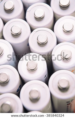 Tops of many AA   white batteries in closeup on wooden background - stock photo