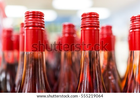 Tops of many red rose wine bottles