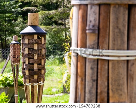 Tops of unlit tiki torches in a yard - stock photo