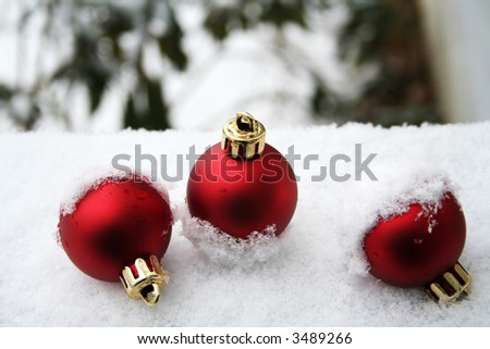 Topsy turvy ornaments in the snow - stock photo