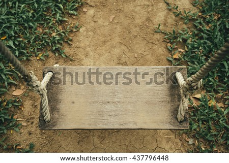 topview image of old wooden swing with grass and ground texture background, vintage tone style