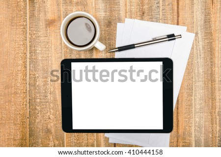 Topview of aged wooden desktop with blank white tablet, coffee cup, pen and paper sheets. Mock up