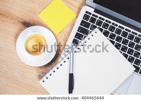 Topview of desktop with laptop, coffee, notepad and yellow stickers - stock photo