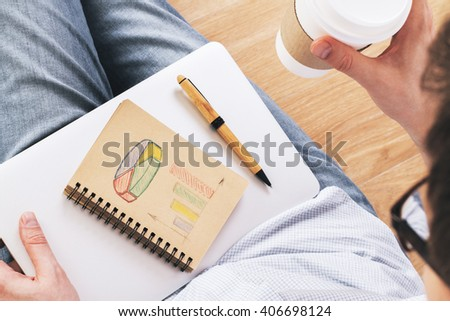 Topview of man drawing business chart in aged notepad placed on closed laptop. Wooden background