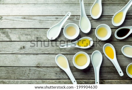 Topview of several soup spoons and sauce dishes filled with different colored oils - stock photo