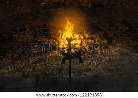 torch on the wall of an old castle - stock photo