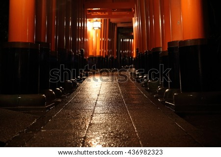 Tori gates in Fushimi Inari Shrine at night with selective focus and blur , Kyoto, Japan