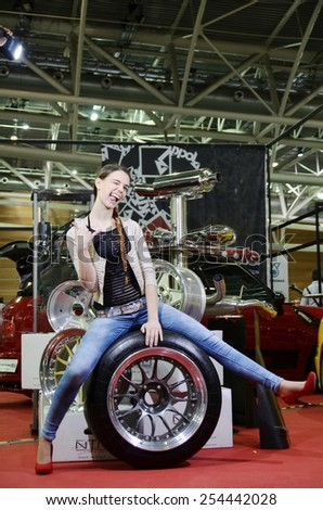 TORINO, ITALY - FEBRUARY 15, 2015: beautiful model with high heels smiling and sitting on custom big sportive car wheels on display at Expo Tuning Torino. - stock photo