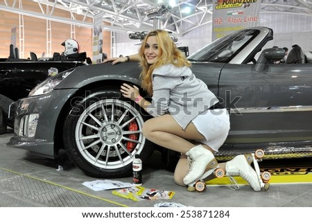 """TORINO, ITALY - FEBRUARY 15, 2015: Beautiful young blonde woman with roller cleaning car tyre and wheel of a special version of tuning Opel Gt cabrio at """"Expo Tuning Torino"""" on February 15, 2015 - stock photo"""