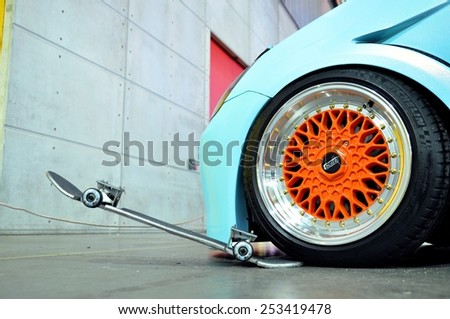 TORINO, ITALY - FEBRUARY 15, 2015: close up of special colored tuned  and sportive car wheel above skatebord exposed at Expo Tuning Torino in Torino business place on February 15, 2015 - stock photo