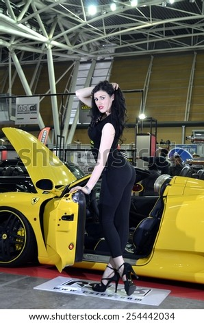 TORINO, ITALY - FEBRUARY 15, 2015: special version of yellow Ferrai 360 spider f1 tuned with sensual and young model with high heels posing at Expo Tuning Torino on February 15, 2015 - stock photo