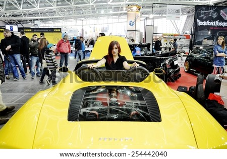 TORINO, ITALY - FEBRUARY 15, 2015: special version of yellow Ferrari 360 spider F1 tuned car with sensual and young model hostess, or pinup, inside posing at Expo Tuning Torino on February 15, 2015 - stock photo
