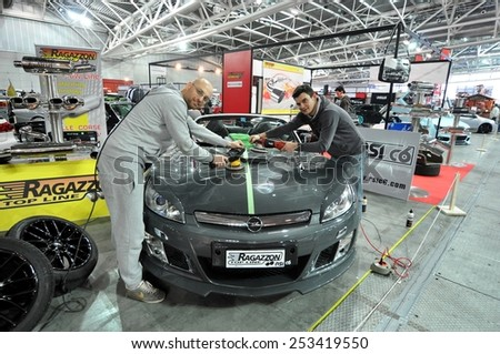 TORINO, ITALY - FEBRUARY 15,  2015: Two guys working with orbital polisher above a sportive bonnet tuned car inside a motor show business place on February 15, 2015 - stock photo