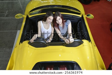 TORINO, ITALY - FEBRUARY 15, 2015:  Two young women inside a new luxury sportive yellow convertible car Ferrari 360 Modena F1 spider at Expo Tuning Torino on February 15, 2015 - stock photo