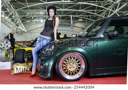 TORINO, ITALY - FEBRUARY 15, 2015: Young and sensual female pilot with helmet posing in front of a Mini Cooper S John Cooper Works tuned car with gold wheels at Expo Tuning Torino on February 15, 2015 - stock photo