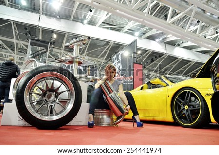 TORINO, ITALY - FEBRUARY 15, 2015: Young attractive and sensual female pin up posing inside a show room with a sportive car mufflers at Expo Tuning Torino motor show on February 15, 2015 - stock photo