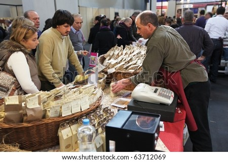 TORINO, ITALY - OCT. 24: People buy local food products in exhibition at Salone del Gusto, international fair of tastes and slow food October 24, 2010 in Torino, Italy. - stock photo