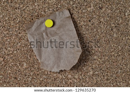 Torn and wrinkled piece of brown paper grocery bag attached to corkboard with yellow pin ready for your message - stock photo