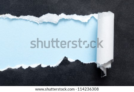 Torn black paper edge with blue space for your message - stock photo