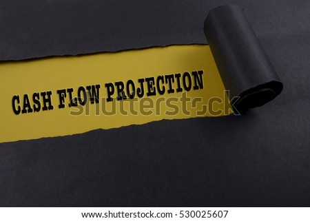 "Torn black paper on yellow surface with ""cash flow projection"" word. Business concept"