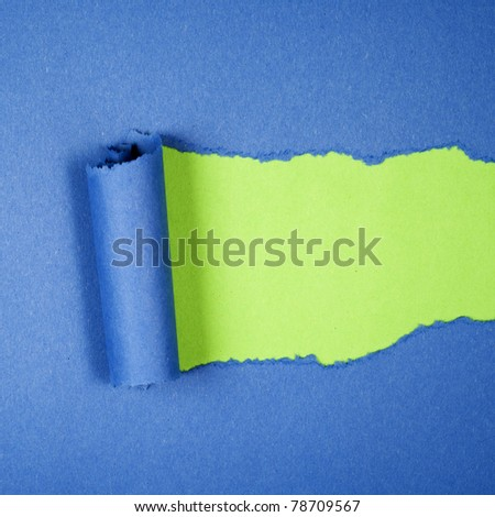 Torn blue color paper on green color background with space for text