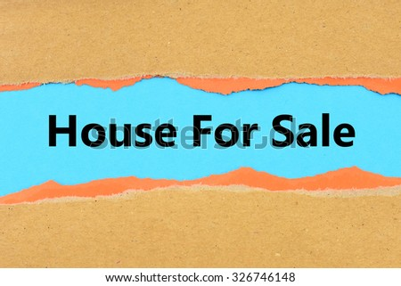 Torn brown and orange paper on blue surface with House for sale words. - stock photo
