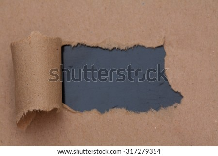 Torn brown color paper with space for text with black background - stock photo
