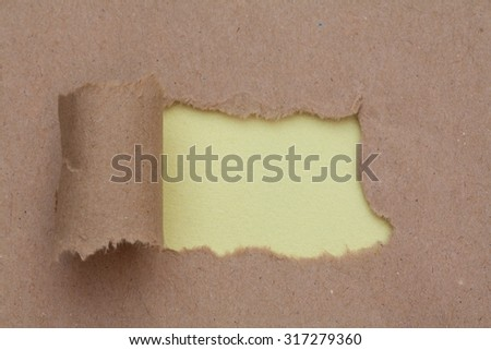Torn brown color paper with space for text with yellow background - stock photo