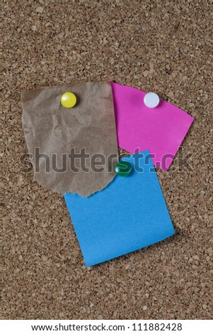 Torn brown paper bag, pink paper and blue paper notes attached to brown corkboard with yellow, white and green pins. Plenty of room for text.