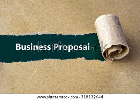 "Torn brown paper on green surface with ""Business Proposal"" words. - stock photo"