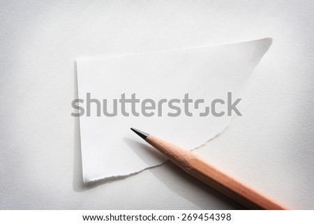 Torn corner piece of memo paper on white desk, with by-the-window type lighting. - stock photo