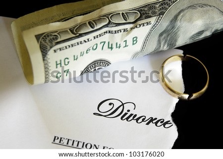 torn divorce decree and cash, with broken wedding ring - stock photo