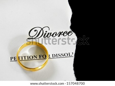 torn divorce decree with gold wedding ring - stock photo