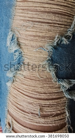 Torn frayed hole in blue denim texture.  - stock photo