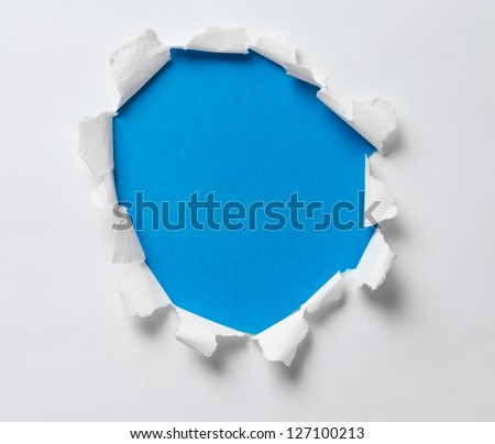 torn hole on the paper with blue background