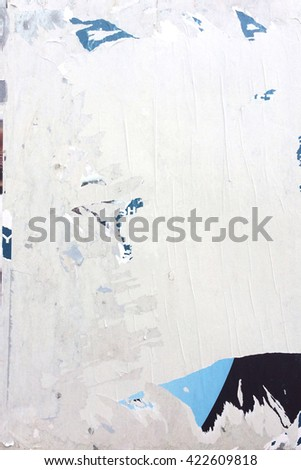 Torn paper background. City wall with torn paper advertising. Grunge urban texture. Messy bulletin board - stock photo