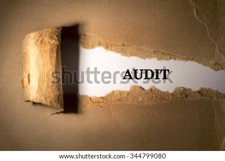 Torn paper box with word audit in low light - stock photo