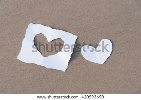 Torn paper heart on sand beach