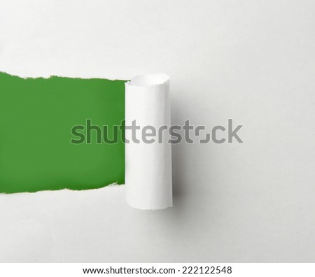 Torn paper in front of a green background - stock photo