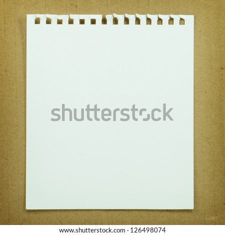 Torn paper on brown paper background. - stock photo