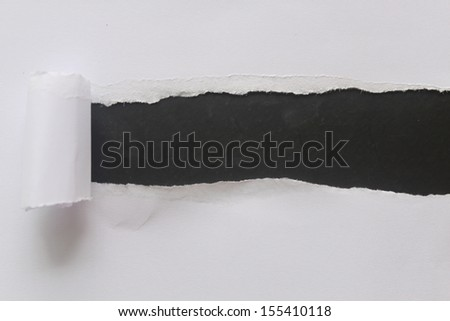 Torn paper over a blank black background for message - stock photo