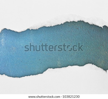 Torn paper over blue wooden background