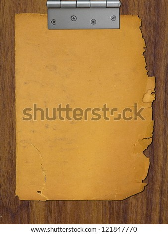 Torn paper pinched in hinge on wood background