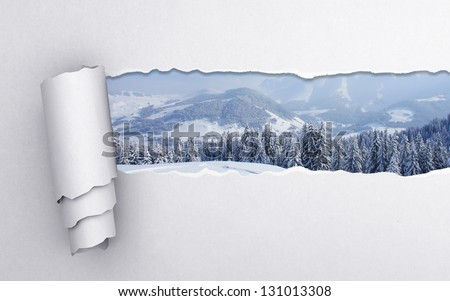 torn paper with winter landscape background - stock photo